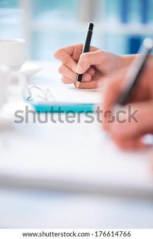 Vertical image of hands making notes at the conference on the foreground  - stock photo