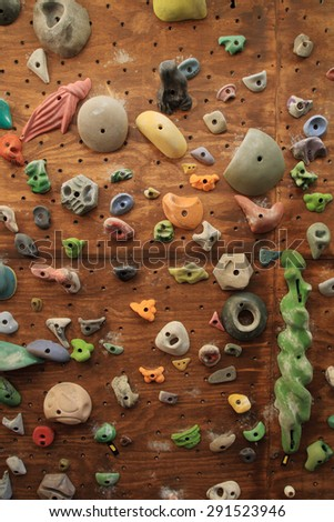 vertical image of homemade indoor artificial climbing wall covered with colored holds for rock climbing training - stock photo