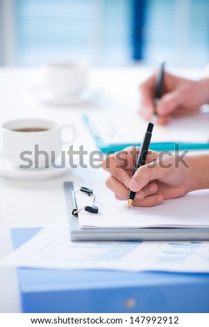 Vertical image of human hands making notes on the business conference - stock photo