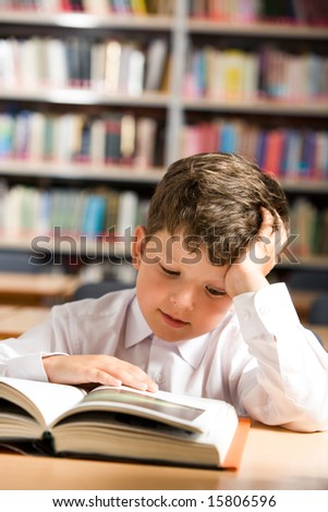 Vertical image of interested schoolkid reading book in the library