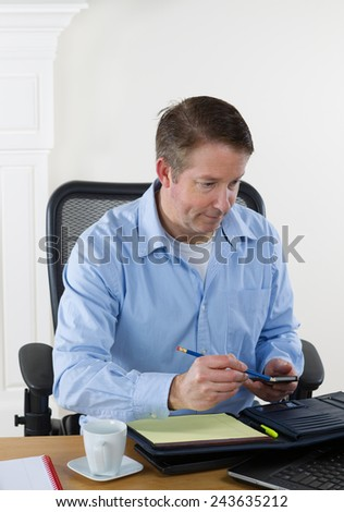 Vertical image of mature man looking at laptop, with pencil and cell phone in hand, while working. White walls in background.