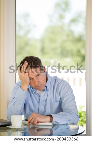 Vertical image of mature man showing depression by holding his head in one hand while working from home with bright daylight coming in from window in background - stock photo