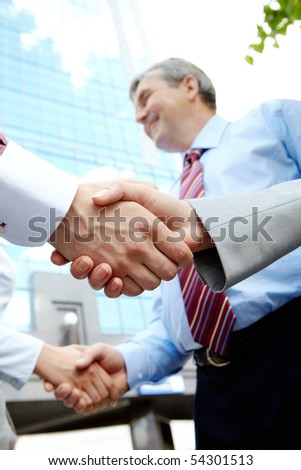 Vertical image of rows of partners handshaking outdoors on background of modern building - stock photo