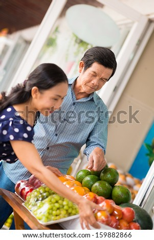 Vertical image of seniors choosing the fruits and vegetables in the store on the foreground - stock photo