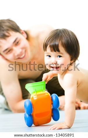 Vertical image of small baby holding toy while her father looking at her from behind - stock photo