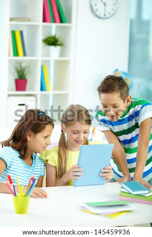 Vertical image of three kids learning how to use a tablet - stock photo