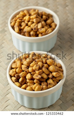 Vertical image of two white bowls with dried corn beans over the mat