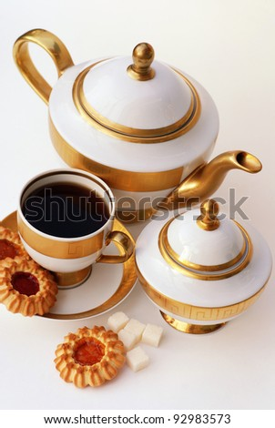 Vertical image with elegant gold and white tea service and cookies - stock photo