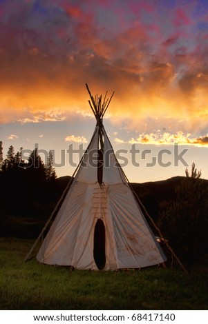 Vertical images of an Indian Teepee high up in the  Mountains with a colorful sunset in the sky. - stock photo
