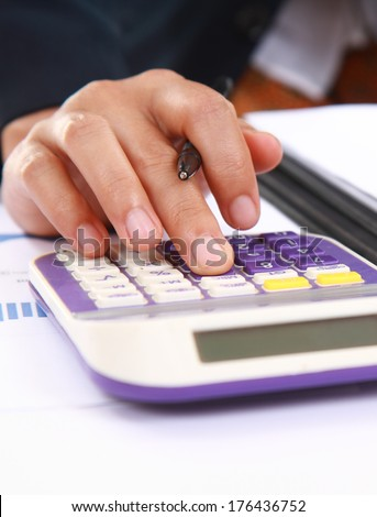 Vertical images of woman's hands with a calculator and a pen, analyzing financial data - stock photo