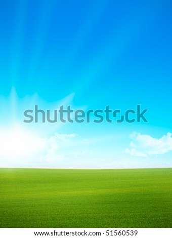 Vertical landscape with green grass and blue sky. on the left side there is the sun and some clouds. Photo was taken on the morning.