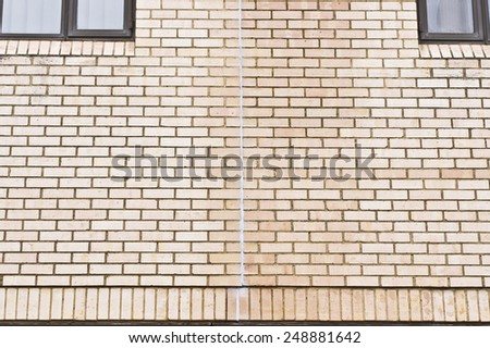 Vertical line of sealant on an external brick wall - stock photo