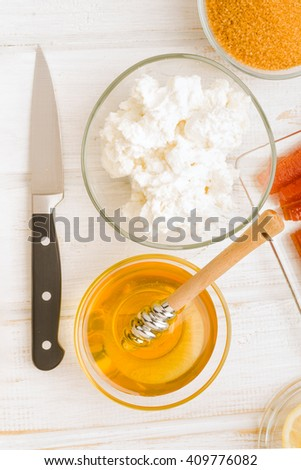 Vertical making bowl of cottage cheese with honey and other products