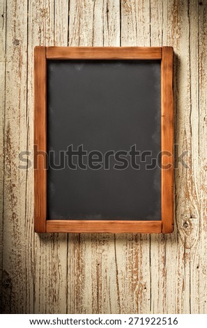 vertical old chalkboard on aged wooden wall - stock photo
