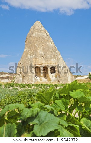 Vertical old limestone cave historically a community church and meeting place. Cushions for seating remain on patio. Surrounded by agricultural farmland with potato crops, shot  in Cappadocia, Turkey - stock photo