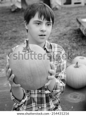 vertical orientation black and white image of an attractive teenage boy with autism and down's syndrome holding a pumpkin / Fall Activities for Children with Autism - stock photo