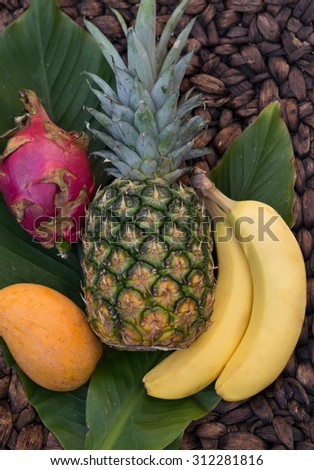 vertical orientation close up of a pineapple, bananas, dragon fruit and mango against banana palm leaves and a textured background / Tropical Fruits - Vertical Orientation - stock photo