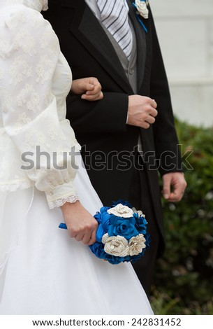 vertical orientation close up of the torsos of a man and a woman in wedding attire, arm in arm, with copy space, in an outdoor setting / Man and Wife - Vertical - stock photo
