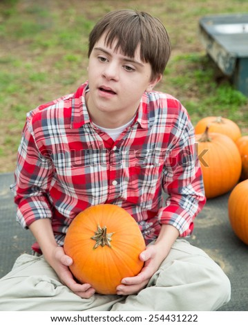 vertical orientation color image of an attractive teenage boy with autism and down's syndrome, sitting cross legged as he holds a small pumpkin / Pumpkin of Choice