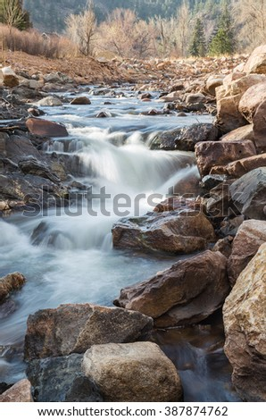 vertical orientation color image, taken with a very slow shutter speed to show the movement of water in a creek through a rocky landscape / Rocky Mountain waterfall and scenery - stock photo