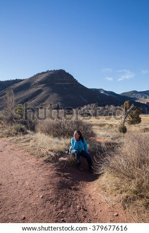 vertical orientation color image with a single woman hiker resting on a rock in the foreground, and mountain scenery in the background / Woman Hiker resting on a Sunny Day - stock photo
