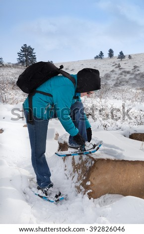 vertical orientation color image with a woman in bright colors with snowshoes in the foreground, and snowy mountainous terrain in the background, with copy space / Adjusting Snowshoes for Traction - stock photo