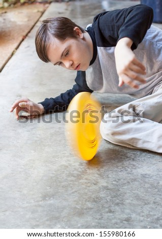 vertical orientation of a boy with autism and down's syndrome looking intently at a round, yellow, object he is spinning on a cement floor, with copy space /  Signs of Autism - stock photo