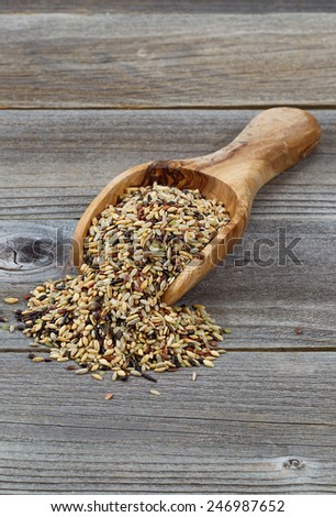 Vertical orientation of a wooden scoop filled with whole grain rice spilling onto rustic wood - stock photo