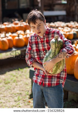 vertical orientation of boy with autism and down's syndrome in a bright red plaid shirt holding a large squash in his arms with pumpkins in the background / Visit to the Farm - stock photo