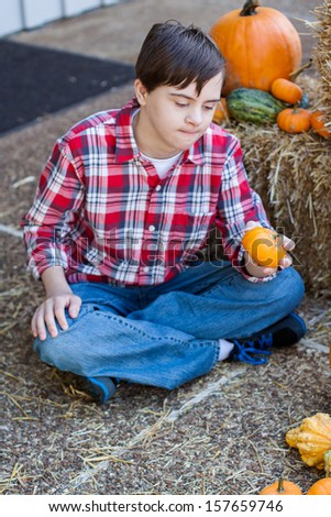 vertical orientation of boy with autism and down's syndrome seated outside on a sunny day with hay and harvest vegetables around him and copy space / Boy with Autism Shops for the Perfect Pumpkin - stock photo