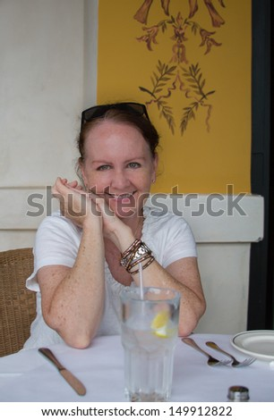 vertical orientation of single, happy, smiling woman in a restaurant with linen tablecloth, place setting and full glass of water with copy space / Foundation for Hydration - stock photo
