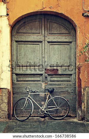 Vertical oriented image of bicycle leaning against old wooden door at the entrance to house on rainy day in Alba, Italy. - stock photo