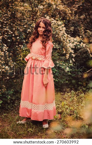vertical outdoor portrait of curly child girl dressed as fairytale princess with flowering bush on background