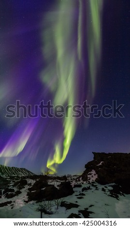 Vertical Panoramic Northern Lights bursting above an Arctic rocky landscape - stock photo