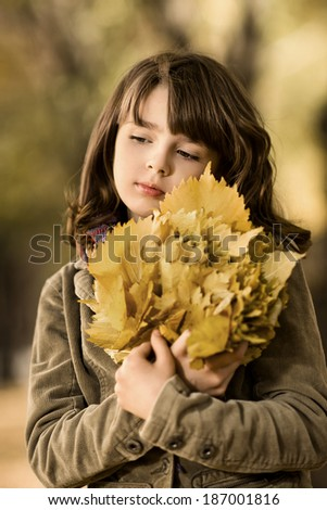 vertical photo, beautiful sorrow little girl hold many yellow leaf, autumnal portrait - stock photo