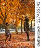 Vertical photo,  happy beautiful little girl with mather throw up  autumnal leafage, in park - stock photo