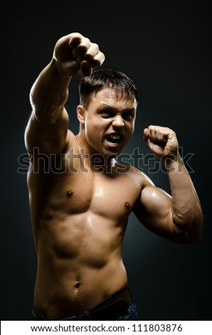 vertical photo  muscular young  guy street-fighter, cuff  fist close up on camera and yell , hard light - stock photo