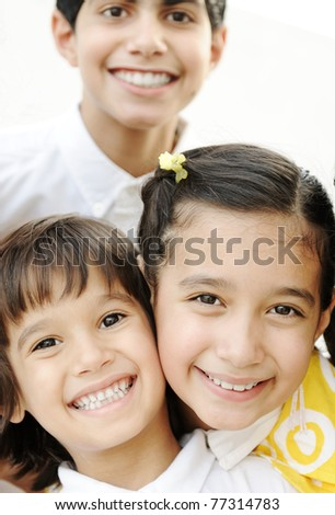 Vertical photo of children group, three friends smiling outdoor, boys and girl closeup - stock photo
