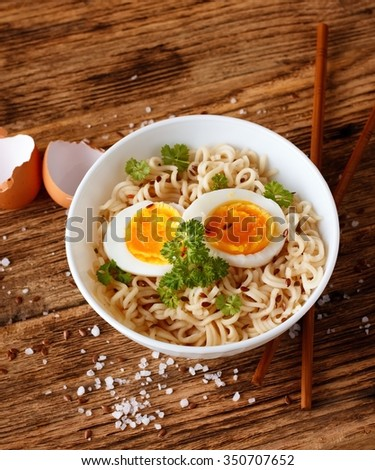 Vertical photo of chinese soup inside white bowl placed on wooden board. Two slices of soft boiled egg are on noodles. Chopsticks, salt and egg shells are around. - stock photo