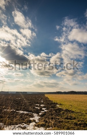 Vertical photo of early spring landscape with dramatic cloudy blue sky. Sun is hidden behind the evening clouds. Field with brown soil and green dry meadow is in front of photo with some snow.