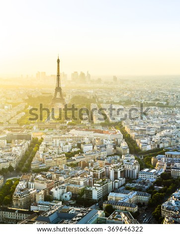 Vertical photo of Eiffel tower in top left of frame with skyline of Paris, France during sunset with soft light