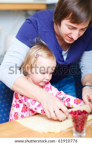 Vertical photo of father and his adorable little daughter baking together - stock photo