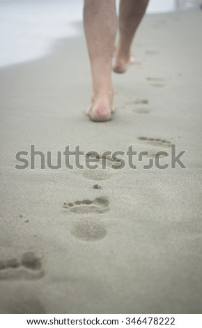Vertical photo of feet of man and footprints on sand of beach on grey cold day with sea defocused in background. Taken in Viareggio in Tuscany Italy on the Mediteranean sea coast.  - stock photo