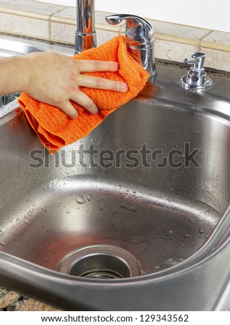 Vertical photo of female hand drying off kitchen sink with microfiber towel - stock photo