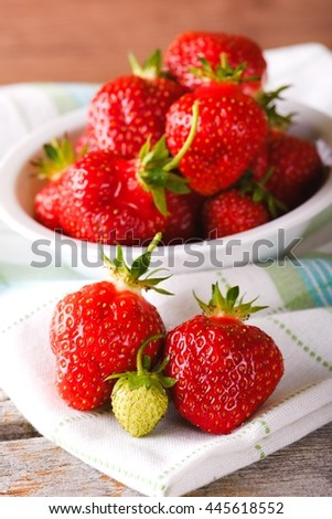 Vertical photo of few juicy strawberries. Single un-ripe green berry with other with red color. Bowel full of ripe strawberries on towel and wooden board with worn surface. - stock photo
