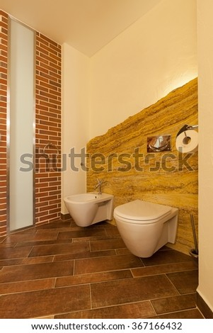 Vertical photo of loft toilet designed in natural brown tones
