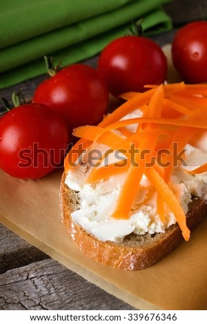 Vertical photo of single slice of bread with fresh cottage cheese. Many shaves from carrot are on with few tomatoes around. All is on dark paper and old grey wooden board.  - stock photo