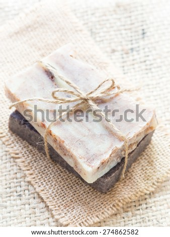 Vertical photo of two bars of homemade all natural hand crafted baobab and chocolate soaps on a burlap background. Overhead view, close up. - stock photo