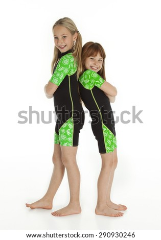Vertical photo of two happy, Caucasian little girls standing back to back wearing wetsuits on white background