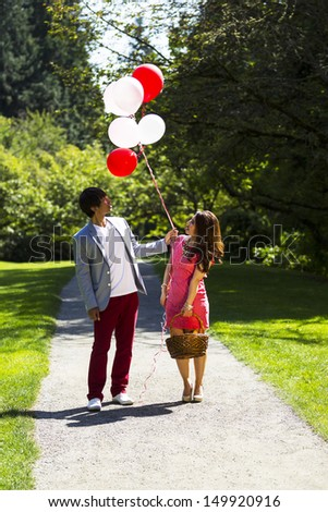 Vertical photo of young adult couple dressed in formal attire looking at several balloons while holding picnic basket with walking path, green grass and trees behind them   - stock photo